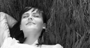 kvinna som ligger ner i gräset och blundar